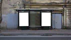 Zwei vertikale leere weiße Anschlagtafeln an der Bushaltestelle auf alter Stadtstraße stockfotografie