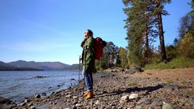 Zwei Videos in einem altai Mountain Lake Fall Die Frau der Reisende in den touristischen Stiefeln geht auf die Küste des Sees stock video