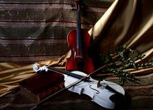 Zwei Violinen auf einem Gewebehintergrund mit einem Bogen und einem Buch Stockfotos