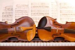 Zwei Violinen auf Klaviertasten Stockfoto