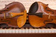 Zwei Violinen, die auf einer Klaviertastatur liegen Stockbilder