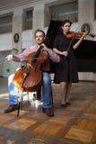 Zwei Violinisten, die zusammen nah Hände oben durchführen stockfotos