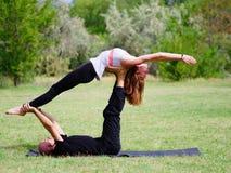 Zwei vom übenden Yoga der Frau im Freien Acro-Yogahaltung Lizenzfreies Stockbild