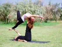 Zwei vom übenden Yoga der Frau im Freien Acro-Yogahaltung Stockfotos
