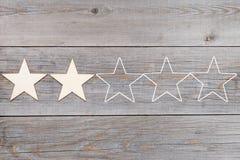 Zwei von fünf Sternen in Folge auf hölzernen Planken, veranschlagendes Konzept stockfotos