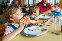 Zwei Vorschulkinder und Vaterjungen, die den Teigwarenhamburger sitzt im Café auf Kreuzschiff essen Glückliche Kinder, Zwillinge  lizenzfreie stockbilder