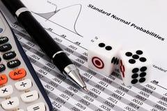 Zwei Würfel, Taschenrechner und Stift auf normaler Wahrscheinlichkeitsstandardtabelle Lizenzfreie Stockfotos