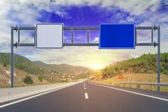 Zwei Wahlen mit leeren Verkehrsschildern auf Landstraße Stockfoto