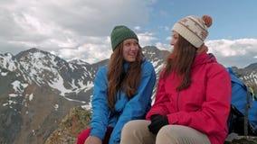 Zwei Wanderer, die auf Hügel sich entspannen und Sonnenaufgang über dem Tal genießen stock footage