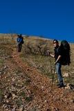 Zwei Wanderer, die oben den Berg steigen Stockfotos