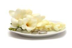 Zwei wedding Platinringe und weiße Blumen Stockbilder