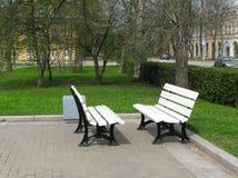 Zwei weiße Bänke stehen gegenüber von einander im Park Bänke lizenzfreie stockfotos