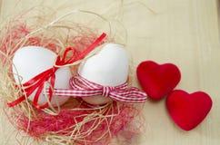 Zwei weiße Eier in einem Nest und zwei Herzen Stockbild