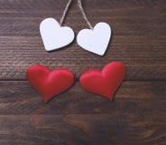 Zwei weiße Herzen und zwei rote Herzen auf braunem Holztisch Lizenzfreie Stockfotografie