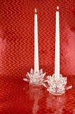 Zwei weiße Kerzen in den Kristallkerzenhaltern mit rotem Backgrounc Lizenzfreies Stockfoto