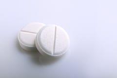 Zwei weiße Pillen auf einer Tabelle stockfoto