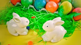 Zwei weiße porctlain Kaninchen nahe bunten hellen Eiern stockbild