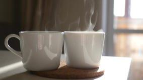 Zwei weiße Schalen mit heißem Kaffee und Dampf in der Sonne Langsame Bewegung 1920x1080 HD stock footage