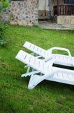 Zwei weiße Stühle auf einem Rasen Stockfotografie