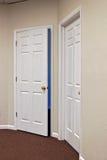 Zwei weiße Türen eine geöffnet Stockbild