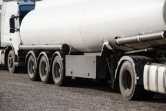 zwei weiße Tankwagen auf der Straße, dem freien Raum und der Leerstelle auf der Zisterne versehen mit Seiten lizenzfreies stockfoto