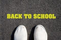 Zwei weiße Turnschuhe auf schwarzem Asphalt Die Aufschrift zurück zu Schule Das Konzept der Bildung Ansicht von oben Lizenzfreie Stockbilder