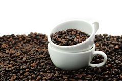 Zwei weißes Cup und viele Kaffeebohnen Stockbild