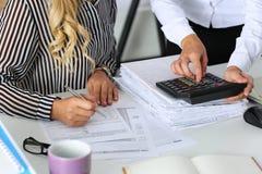 Zwei weibliche Buchhalter, die auf Taschenrechner zählen Stockbilder