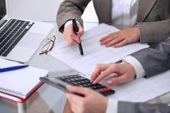 Zwei weibliche Buchhalter, die auf Taschenrechnereinkommen für Steuerformularfertigstellung zählen, übergibt Nahaufnahme Bundesst Stockbild