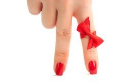 Zwei weibliche Finger mit roter Maniküre als Fahrwerkbeine Lizenzfreie Stockfotos