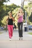 Zwei weibliche Freunde, die auf Straße rütteln Lizenzfreie Stockfotografie