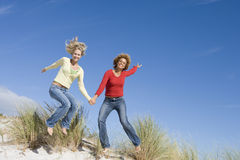 Zwei weibliche Freunde, die Spaß auf Strand haben Stockbild