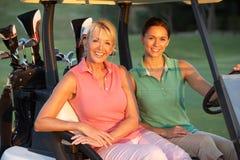 Zwei weibliche Golfspieler, die in Golf-Buggy reiten Lizenzfreie Stockfotos