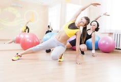 Zwei weibliche kaukasische Athleten im guten Sitz, der die Arme ausdehnen Übungen hat stockfotos