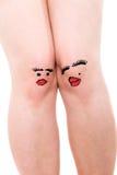 Zwei weibliche Knie mit den Gesichtern, lokalisiert Lizenzfreies Stockfoto