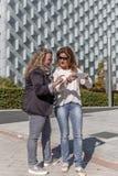 Zwei weibliche Kollegen bei der Arbeit etwas besprechen wichtig vor einem Bürogebäude stockbilder