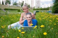Zwei weibliche Kursteilnehmer mit einem Laptop stockfotografie