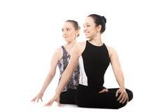 Zwei weibliche Partner des Jogis, die im Yoga Lotus Pose sich entspannen Stockfotografie