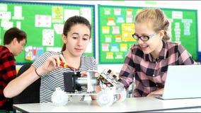 Zwei weibliche Schüler, die Roboterauto in der Wissenschafts-Lektion errichten stock video footage