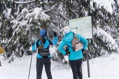 Zwei weibliche Skifahrer, die nach einem Querfeldeinweg auf der Karte suchen Stockfotografie
