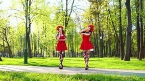 Zwei weibliche Tänzer in den hellen Kostümen führen Volkstanz im sonnigen Park durch stock footage