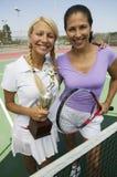 Zwei weibliche Tennis-Spieler durch Netz auf dem Gericht, das Trophäenporträt hält lizenzfreie stockfotos
