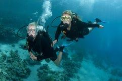 Zwei weibliche Unterwasseratemgerättaucher tauchen zusammen Stockfoto