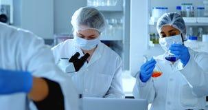 Zwei weibliche Wissenschaftler, die im Labor 4k experimentieren stock video footage