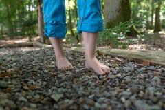 Zwei weiblicher Fuß geht über Kiesel stockbild