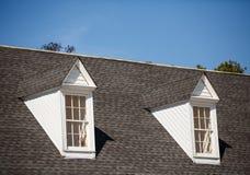Zwei weiße Mansardenfenster auf Grey Shingle Roof Stockfoto