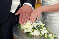 Zwei Weißgoldeheringe auf Rosenblumenstrauß Stockfotos