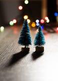 Zwei Weihnachtsbäume auf dem Hintergrund von hellen Geschenken, farbige Lichter, Stockbild