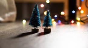 Zwei Weihnachtsbäume auf dem Hintergrund von hellen Geschenken, farbige Lichter, Lizenzfreies Stockbild