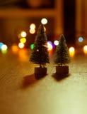 Zwei Weihnachtsbäume auf dem Hintergrund von hellen Geschenken, farbige Lichter, Stockbilder